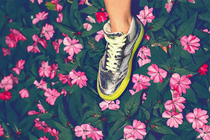 A silver sneaker on a field of pink and green foliage to talk about using pop culture in digital easter eggs