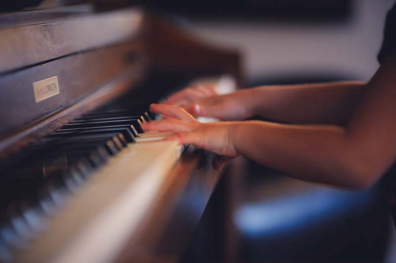 fingers playing a piano