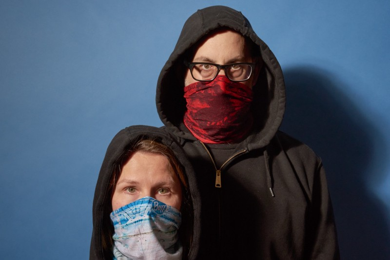 Two people wearing hoodies and facemasks