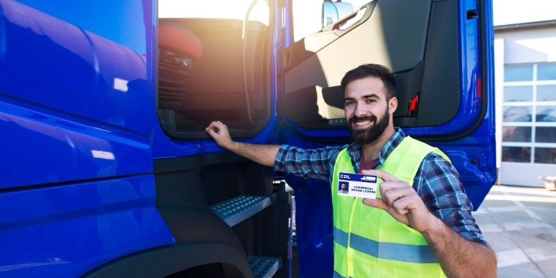Image of truck driver standing in front of rig holding up his CDL license