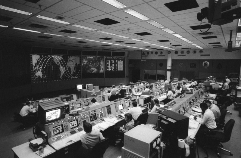 Black and white view of a 1960s NASA mission control room
