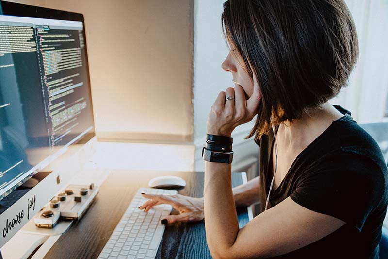 woman in front of screen of code