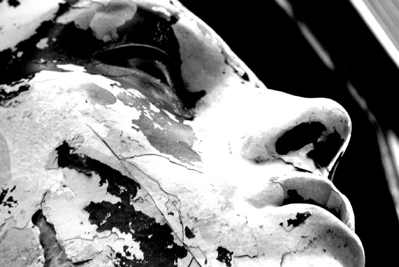 Black and white close up of a white statue with peeling paint, revealing black underneath