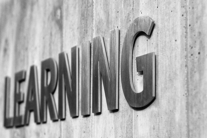 The word learning is spelled out in all capital letters against a concrete wall.