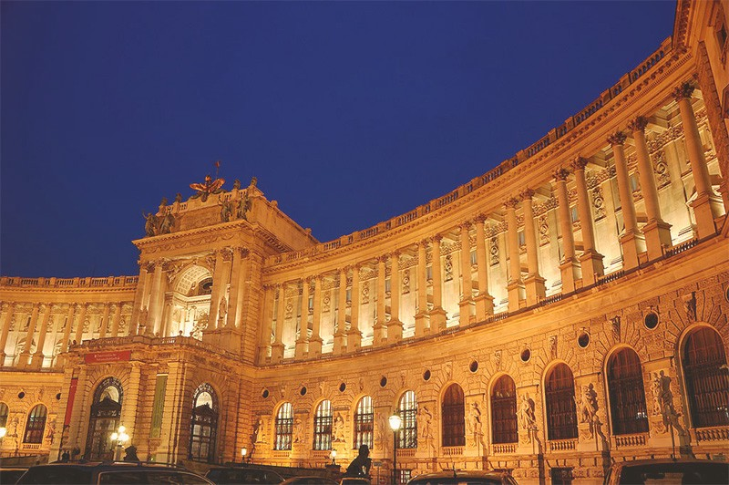 Glowing exterior of the curved Hofburg exterior at night.