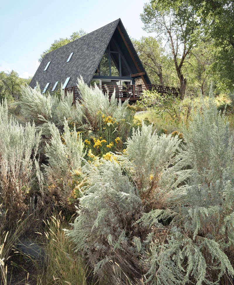 An A-frame house surrounded by plants in Heber, Utah.