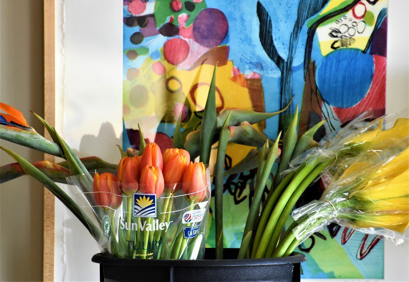 Bright colored modern art painting with flowers in matching colors preparing for a Historic Garden Week house tour