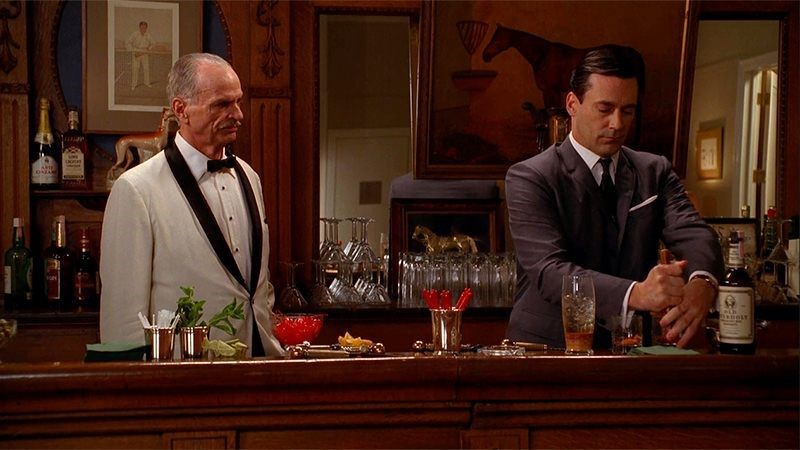 Don Draper stands at a bar with Conrad Hilton making the pair an Old Fashioned cocktail.