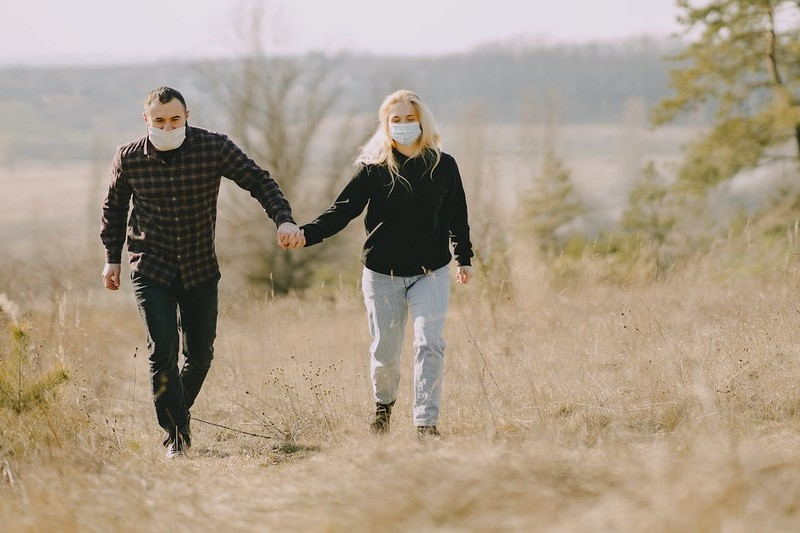 Couple walking in nature, wearing facemasks