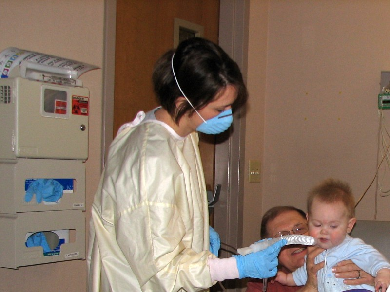Doctor with mouth mask treated a small child