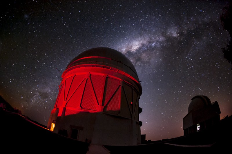 A nighttime picture of a telescope dome seen in red light.