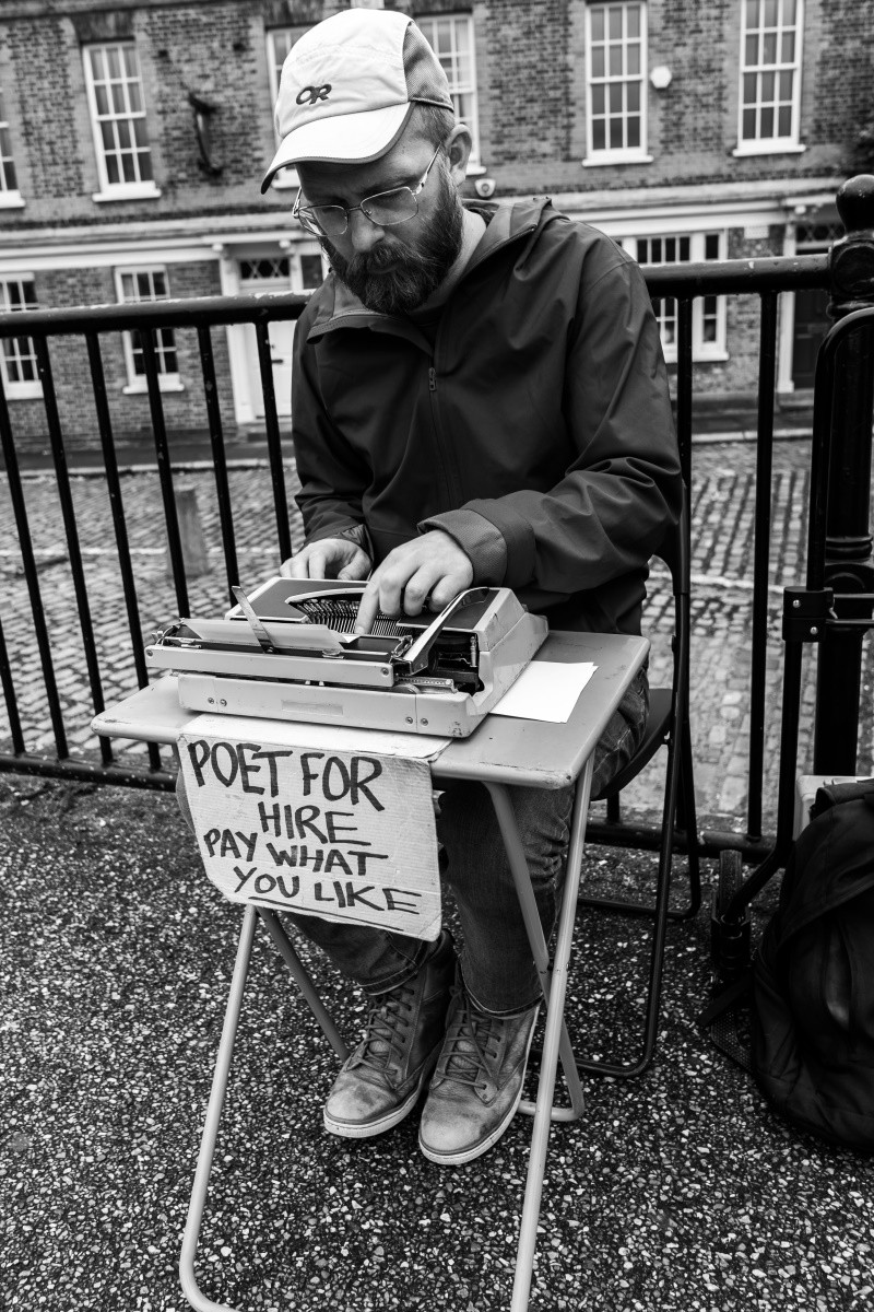 Black and white photo of a man sitting at a small folding table. He is typing on a manual typewriter.