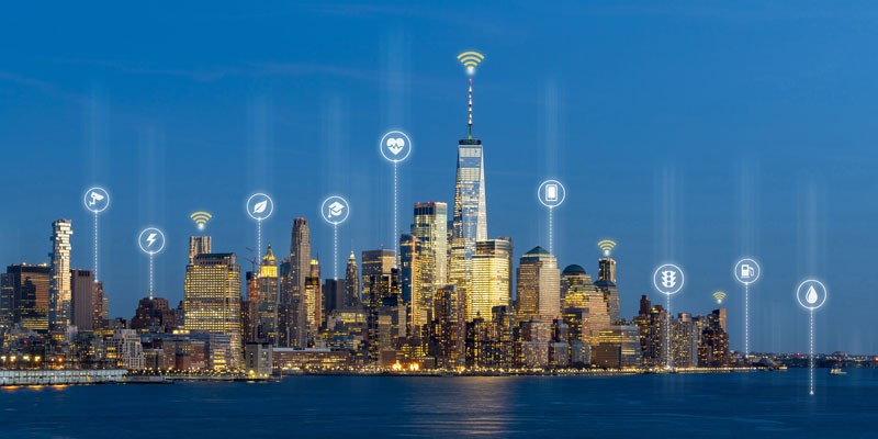 A skyline with hovering smart city icons in white: electricity, health, education
