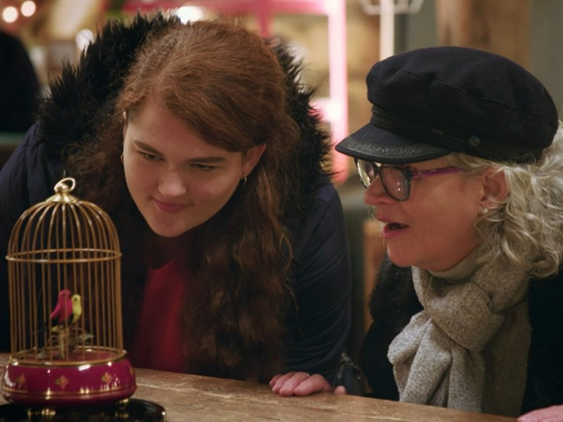 A mother and her daughter looking in awe at a restored mechanical birdcage with two tweeting birds, from The Repair Shop