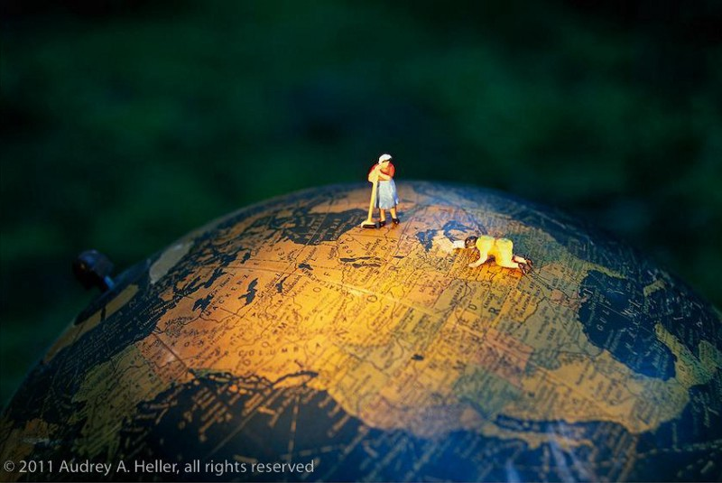 Two women are in the spotlight, cleaning and caring for North America on a desktop globe. Work at Hand by Audrey A. Heller