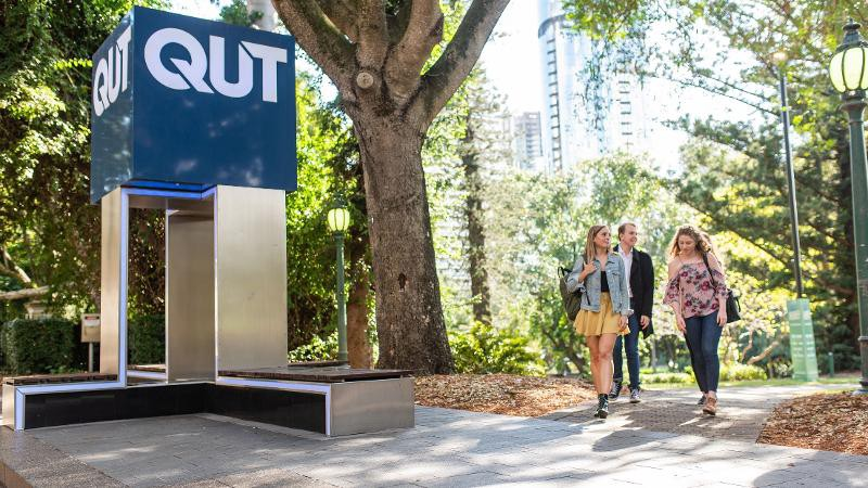 Some students walking through the QUT university campus.
