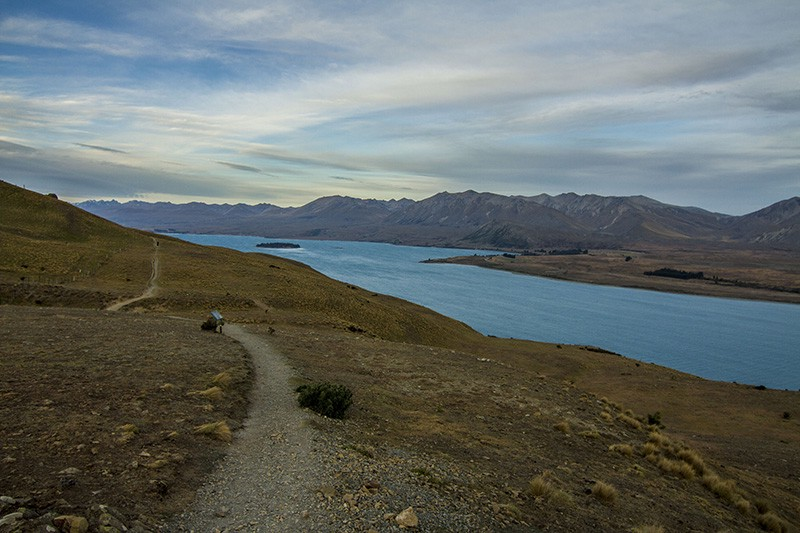 Path along a mountain lakeshore, stretching into the distance