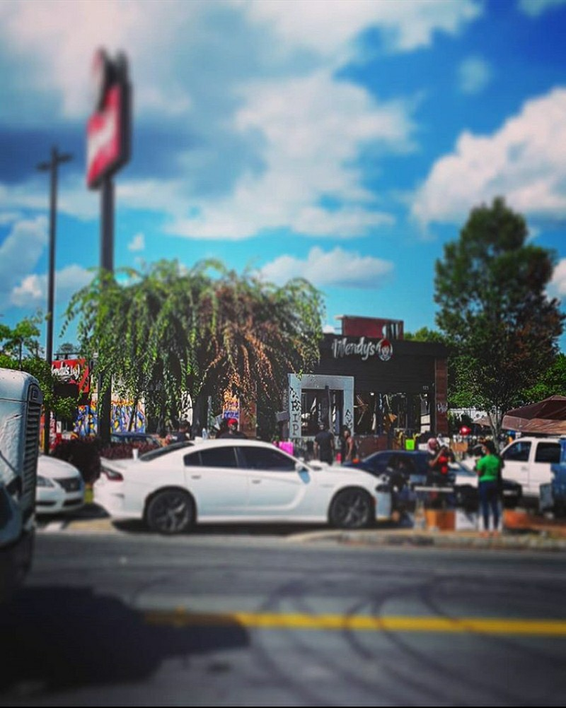 Photo of Wendy's. Taller tree on right, shorter on left. People are gathered and there is a shrine. White car in foreground.