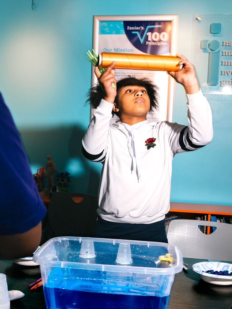 A child looking at a roll of Saran Wrap, in front of a bowl of water, preparing for the Boat Challenge.