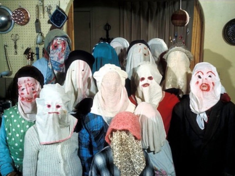 A group of mummers in masks made from bedsheets