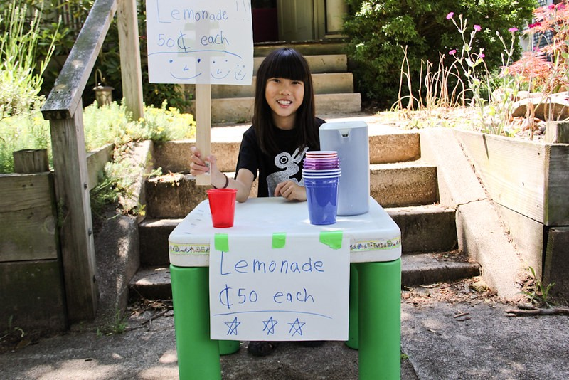 A young girl with a lemonade stand