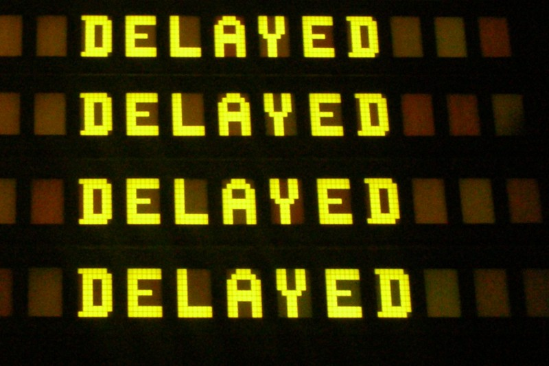 Fragment of Airport departures board, showing 'delayed'