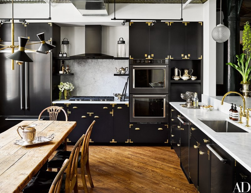 black cabinetry and gold wood floor kitchen by Ken Fulk
