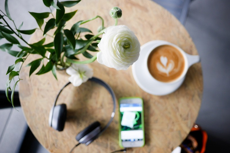 A birds eye view of a cafe table with a big coffee with foam art of a flower and a pair of headphones and an iphone