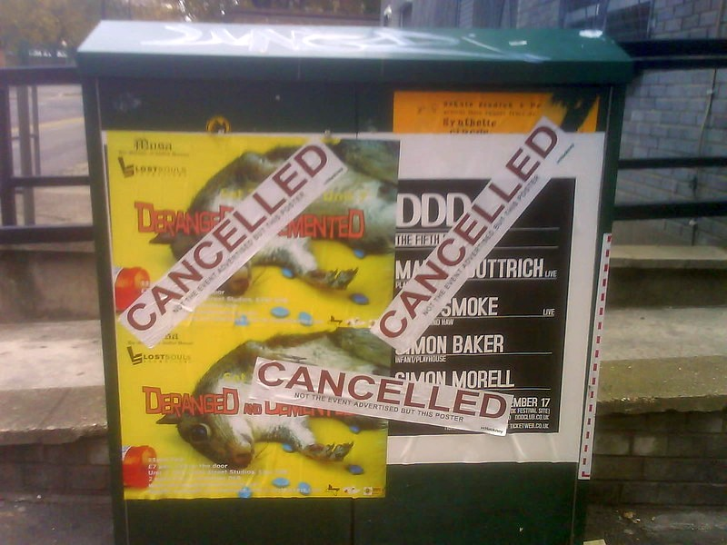 Billboards with concert announcements, with 'cancelled' notices pasted over them