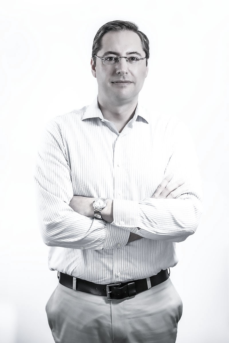 A man in business standing in front of a white background with his arms crossed.