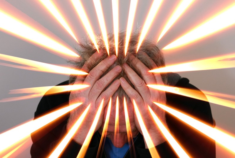 Man with head in hands, and rays of light emanating from his head