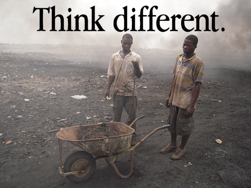 A 2010 photo, 'Agbogbloshie e-waste workers completing a burn for copper recovery'; it is captioned with the wordmark from Apple's infamous 'Think Different' campaign. Image: Jcaravanos (modified) https://commons.wikimedia.org/wiki/File:E-waste_workers.jpg CC BY-SA: https://creativecommons.org/licenses/by-sa/4.0/deed.en