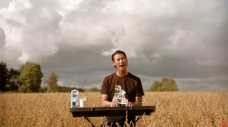 Oatly CEO Toni Petersson playing the keyboard in the middle of a field with a cup and carton of Oatly oat milk to his side.