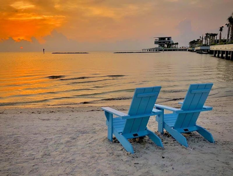 Blue Adironback chairs facing a deep orange sunset over the Bay