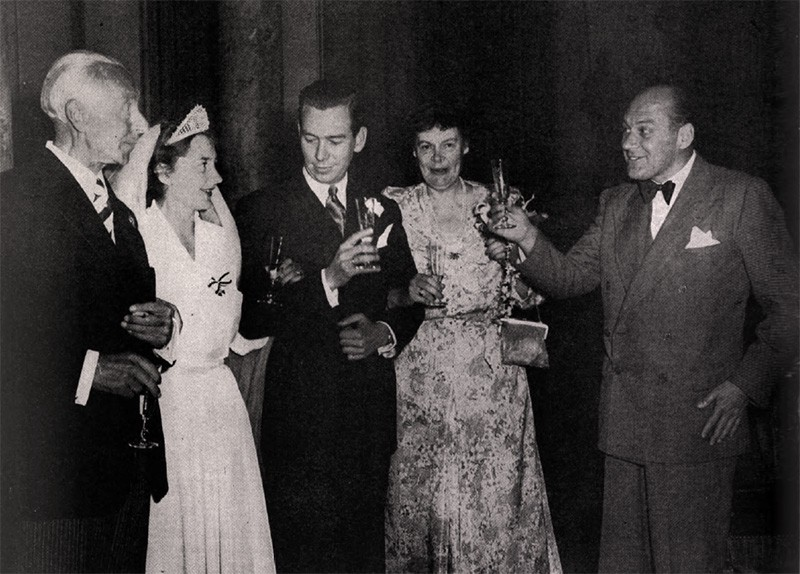 Cecilie in her wedding dress and a triangular tiara next to Clyde, holding a champagne flute. Her parents are on either side.