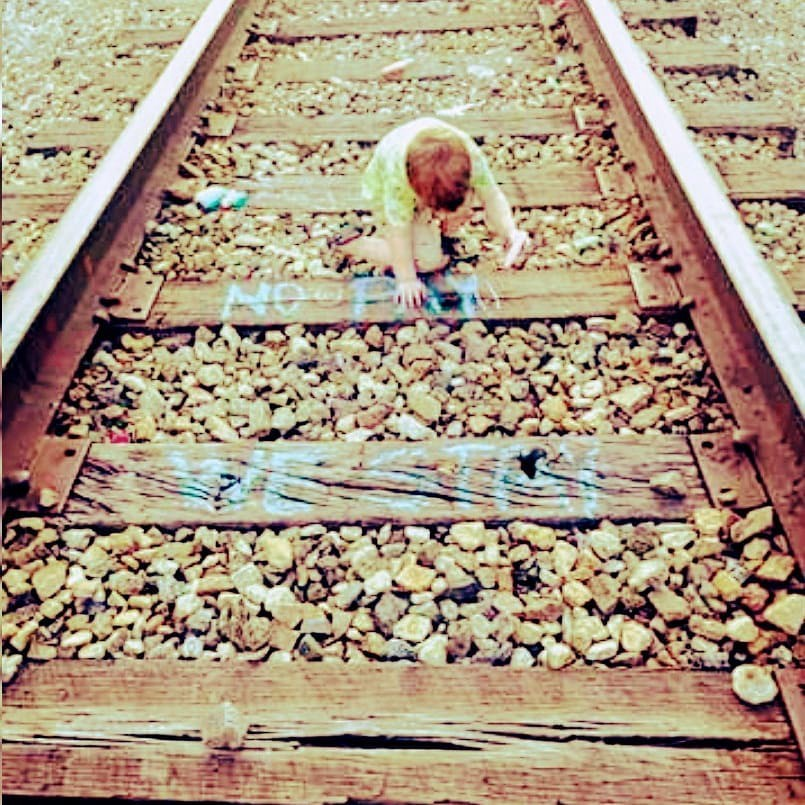A child writing No Pay We Stay on train tracks in Harlan County
