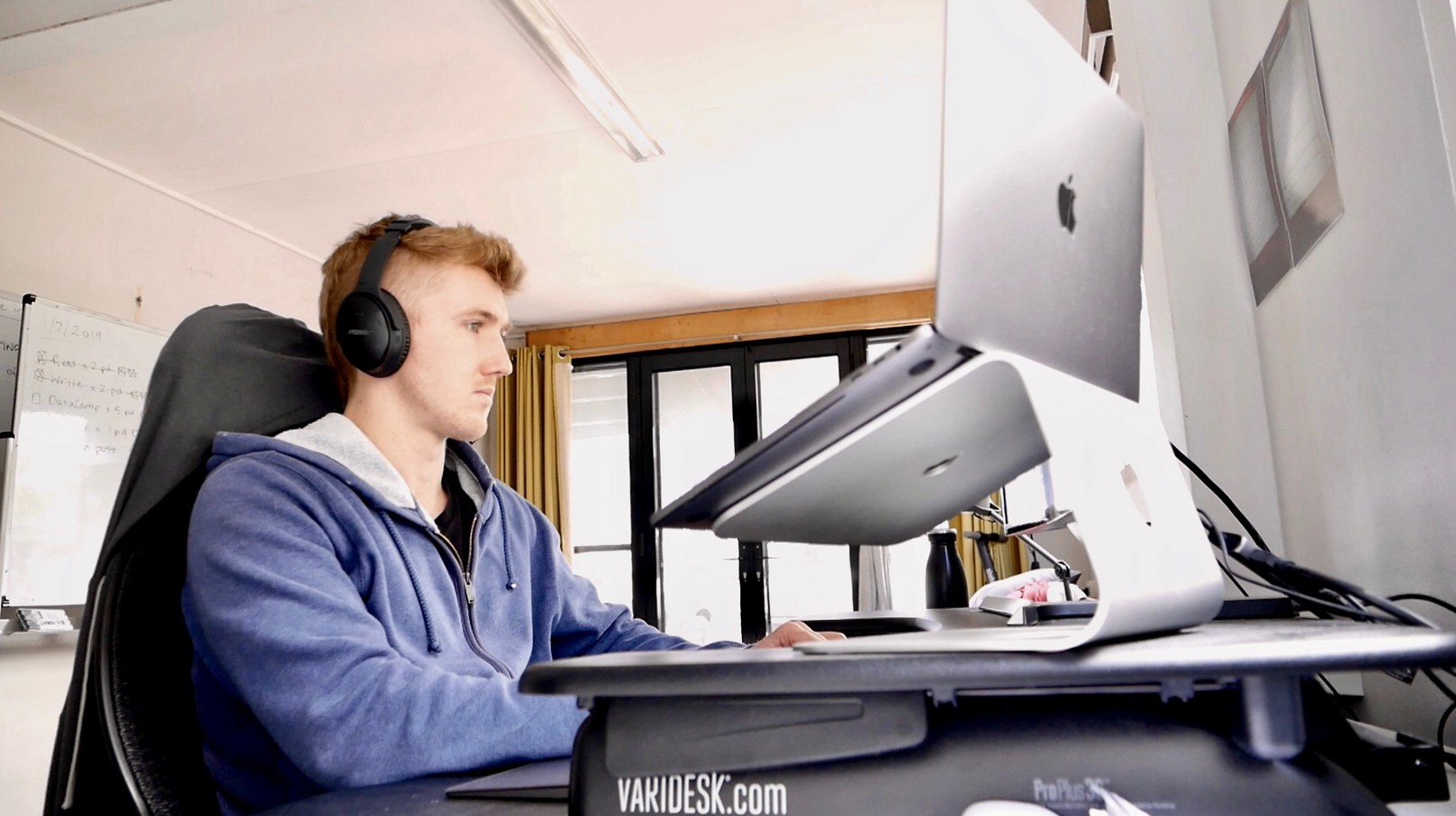 man wearing headphones and sitting at a computer desk