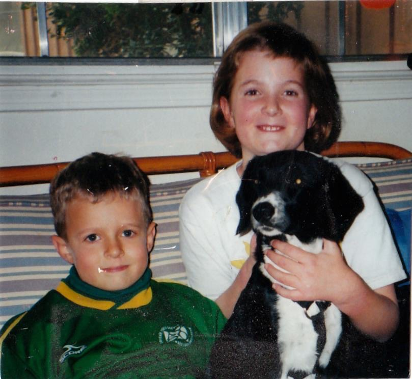 A boy and girl sit on the couch. The girl is holding a black and white dog.