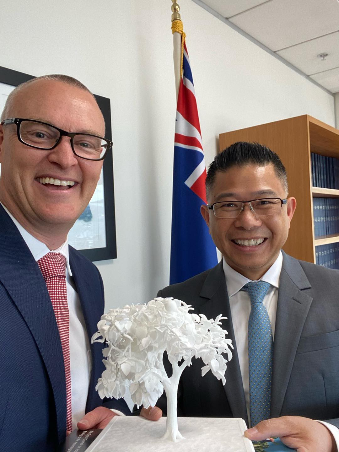 Hon Dr David Clark stands left with Mitchell Pham, right. Between them they hold a small, white 3D printed tree on a stand.