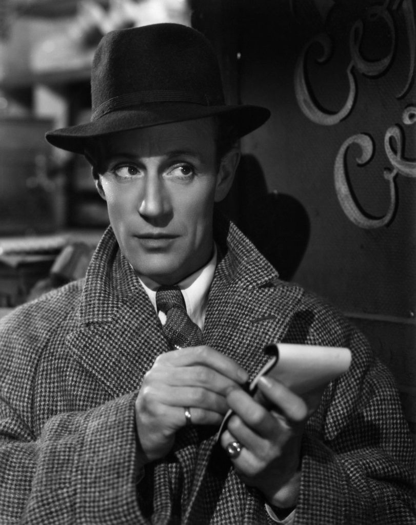 A black & white photo of a white man in a tweed coat, tie, and fedora, taking notes in a notepad & glancing right.