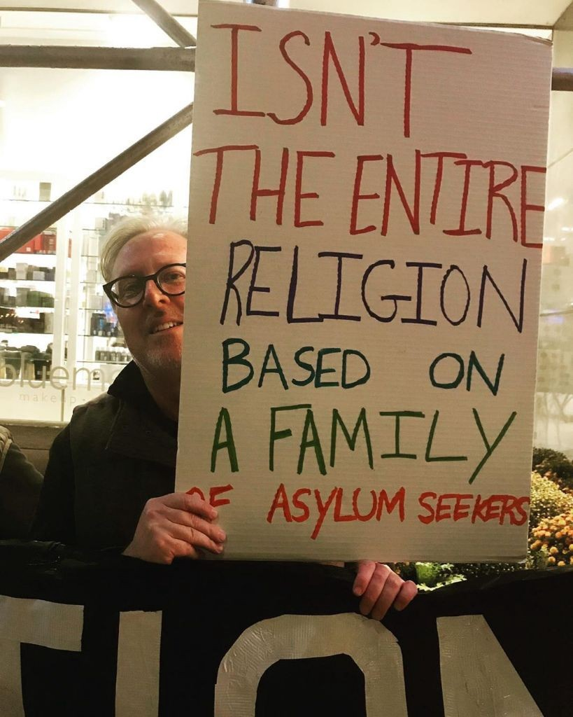 protest sign: isn't the entire religion based on a family of asylum seekers