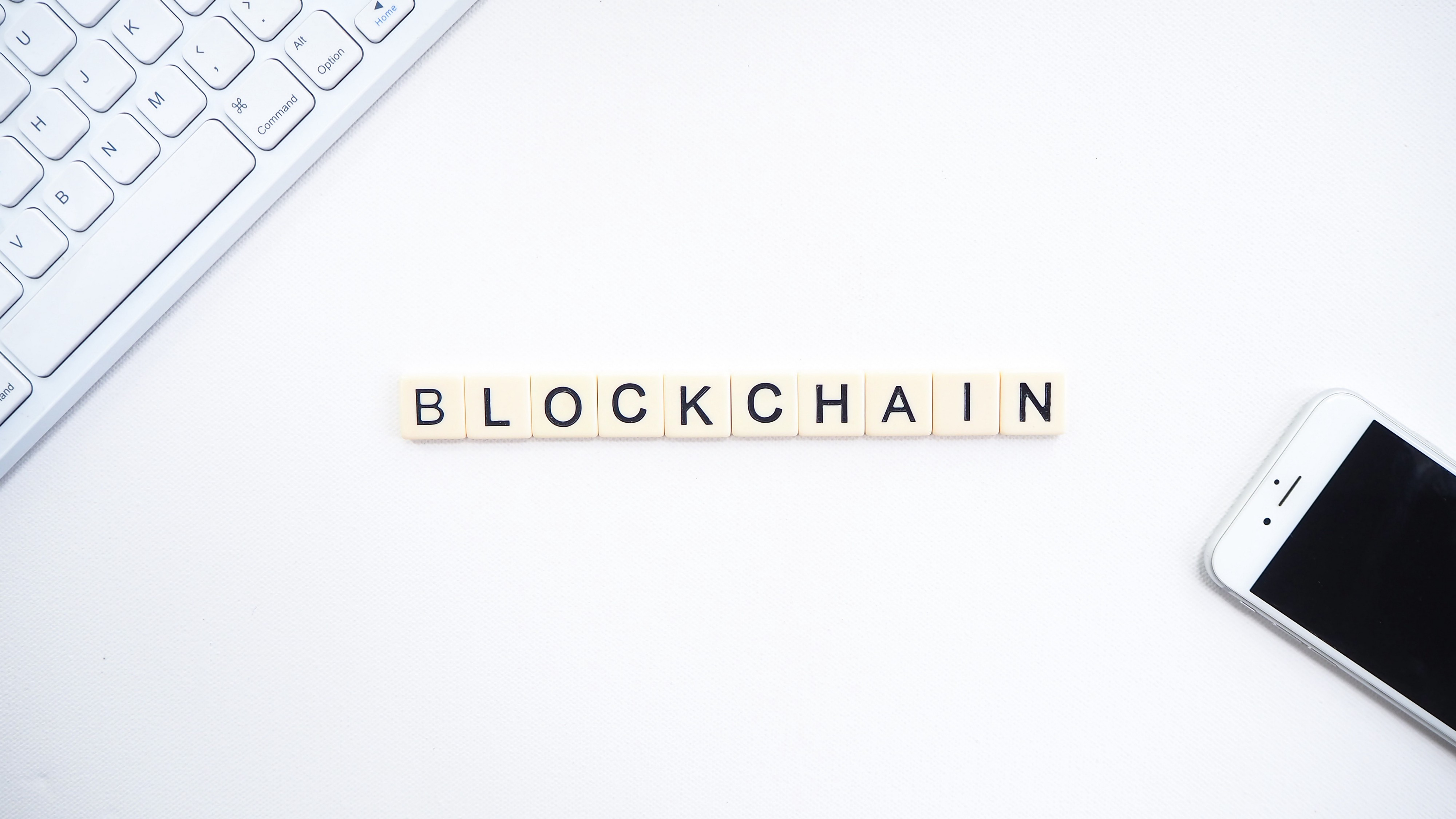 """A picture of some small square pieces with stamped letters spelling """"blockchain"""" on a desk."""