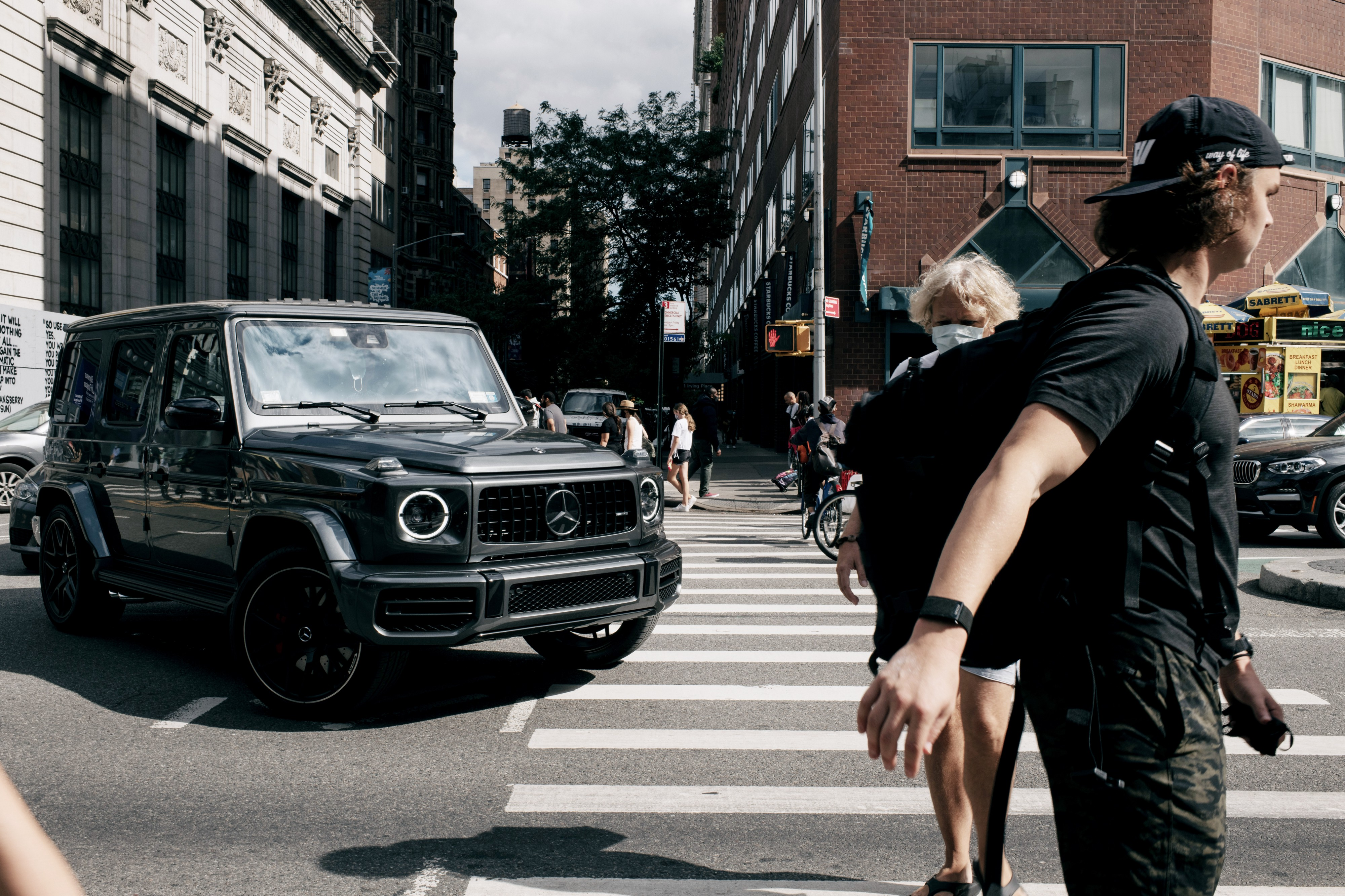 A Jeep turns into a crosswalk, where pedestrians are walking.