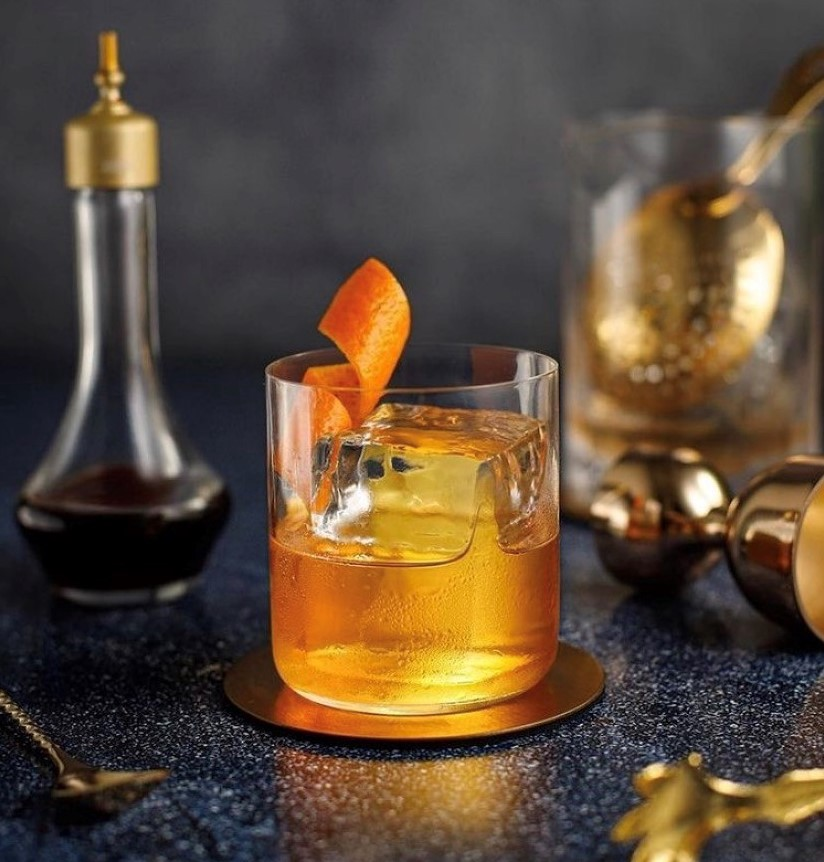Old Fashioned Cocktail in a Modern Glass with a Large Ice Cube and Orange Twist