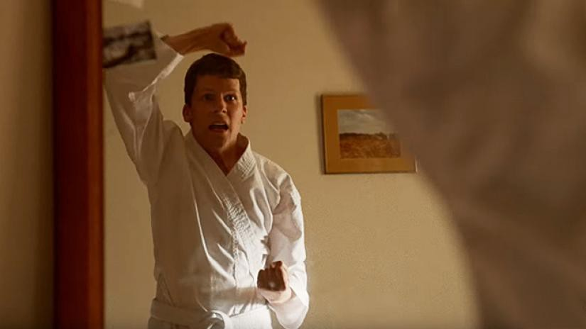Jesse Eisenberg in a white karate uniform practicing moves in a mirror