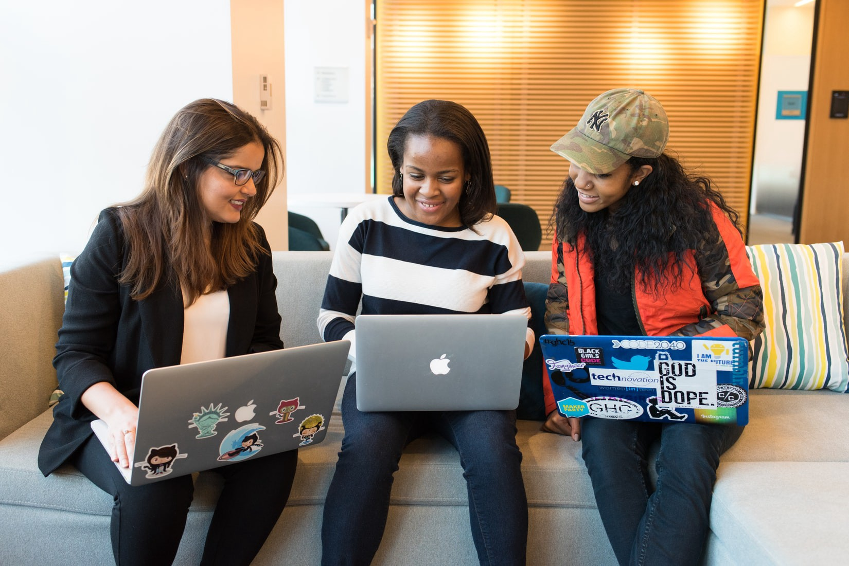 Two dark-skinned and one light-skinned women sitting on a couch with laptops