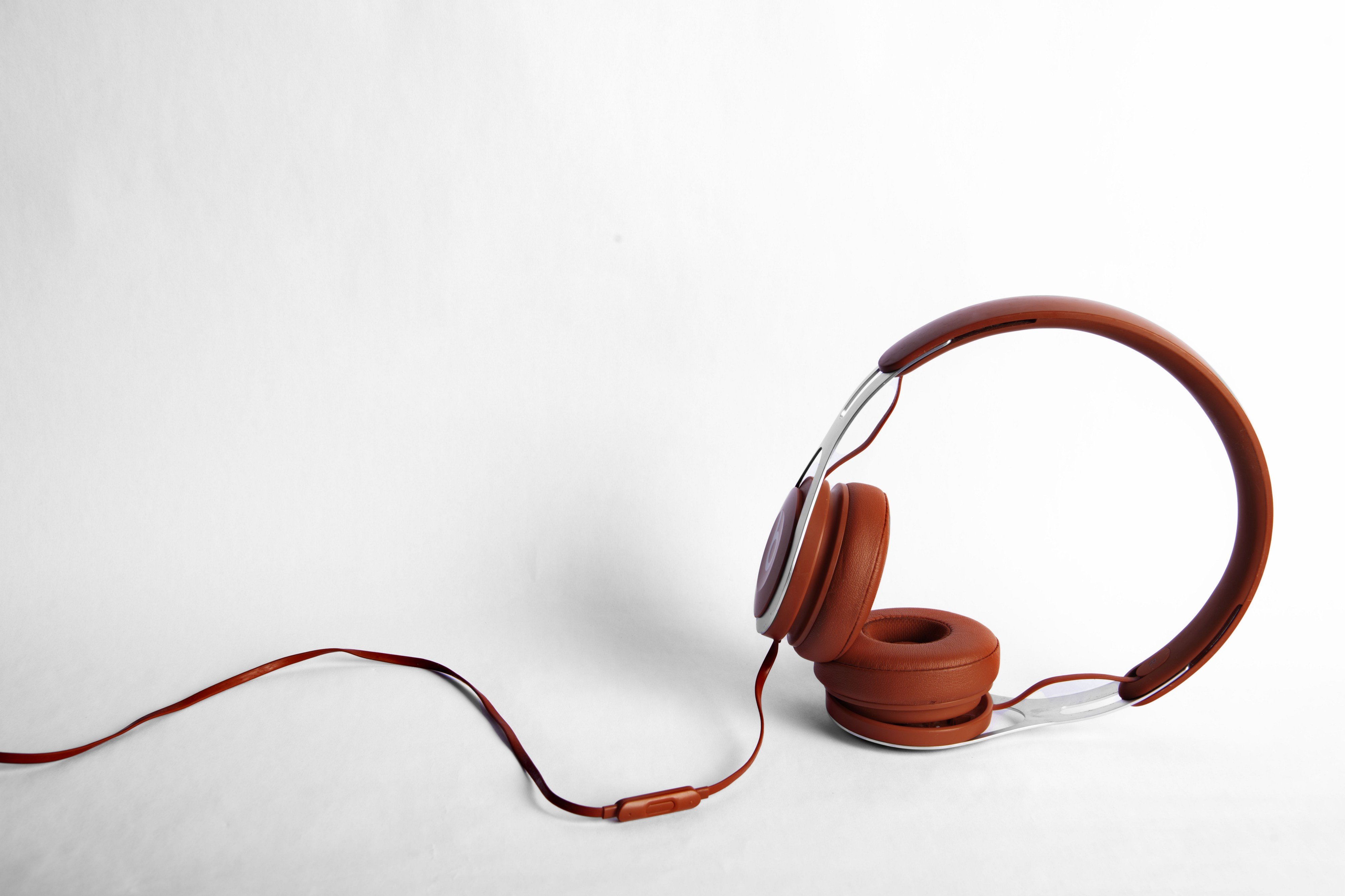 Rust-colored headphones to the right, with the wires trailing to the side