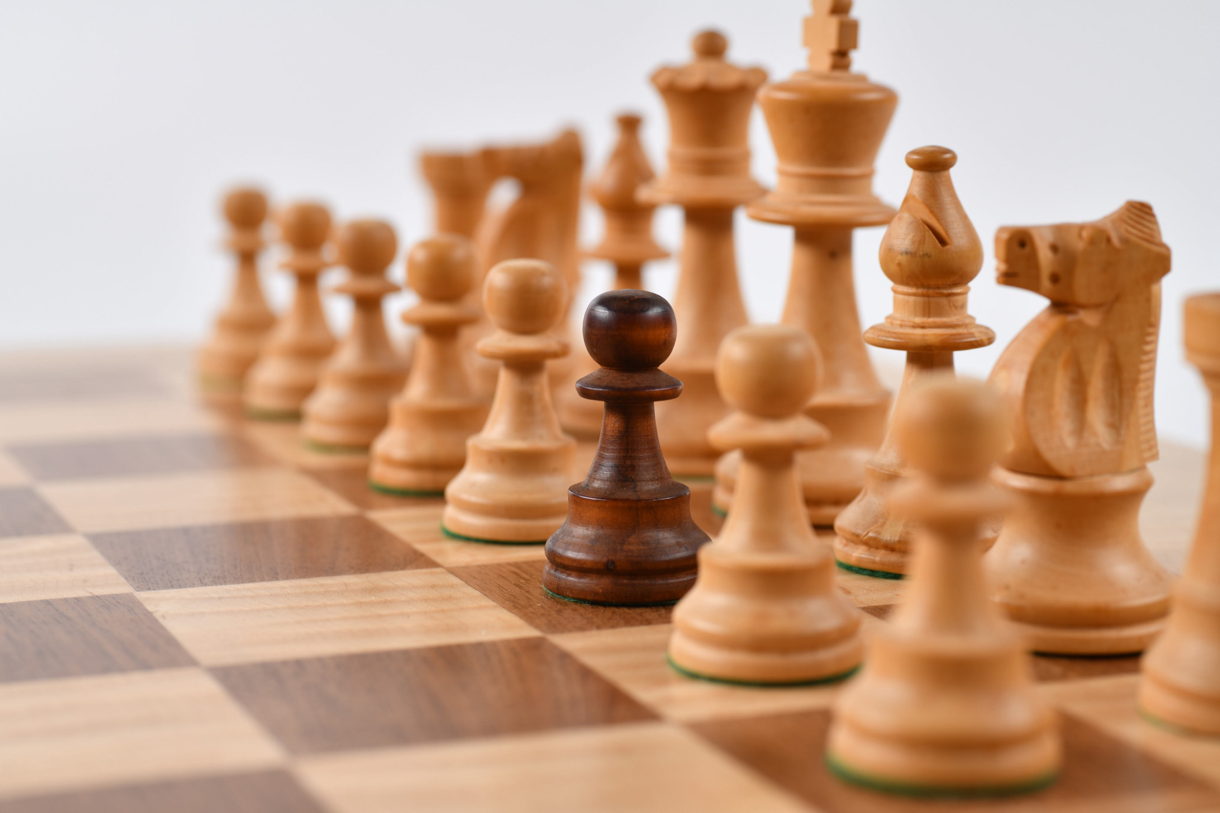 white chess pieces with one rust-colored pawn ready for play