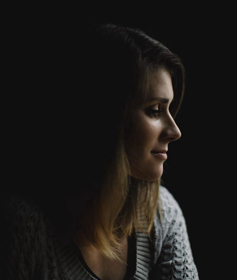 Photo of a white woman in profile in front of a black background.