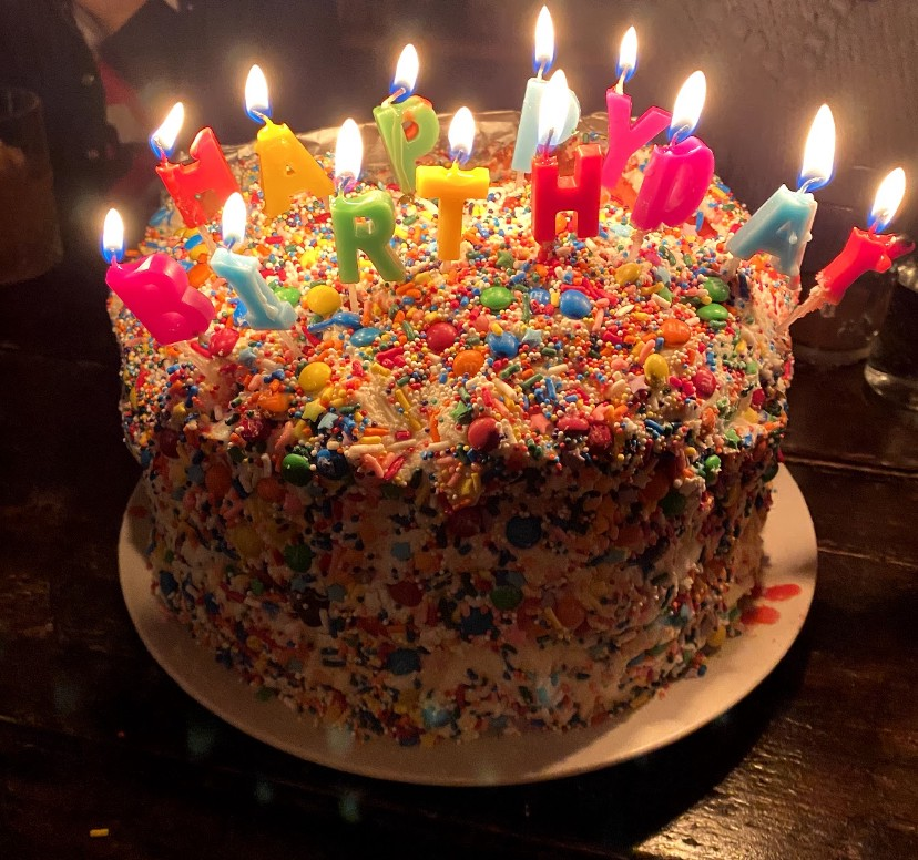 """Rainbow birthday cake lit with """"Happy Birthday"""" candles and covered in sprinkles"""